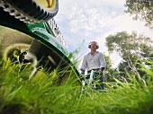 Man mowing lawn wearing ear protectors