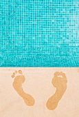 Wet footprints on surround of swimming pool with turquoise mosaic tiles