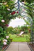 Rose-covered archway in summer garden