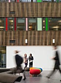 Stools with colourful upholstery in foyer of modern school building