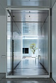 Glass-walled installation in corridor and view of potted tree in courtyard