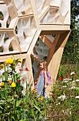 Girl standing in doorway of modern house with wood and plastic facade elements in flowering garden