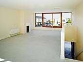Empty room with staircase and view of housing estate through widow