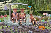 Whimsical terracotta figures made from plant pots in flowering garden