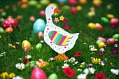 Wooden goose on lawn amongst flowers and colourful Easter eggs