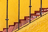 Staircase with sunshine yellow walls, red treads and tiled risers