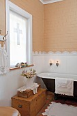 Bathroom with lace border decorating wall and lace-trimmed towels, bathmat & doilies