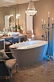 Candlelight atmosphere in modern bathroom with free-standing bathtub and Baroque elements; silver floor candelabra next to bathtub