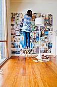 Frau, auf einem Designerstuhl stehend, klebt Fotos an die Wand