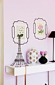 Tour Eiffel made of wire on a white sideboard next to a Chinese vase; picture frames with flower pictures drawn on the wall