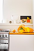 Kitchen shelf with still life; including a yellow shopping bag with fresh fruit