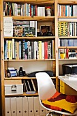 Full shelf wall in study with white shell chair and white desk; a colorful pillow on the chair