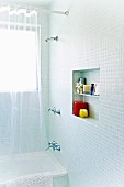 Square wall niche in a mosaic tiled bathroom