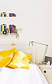 White bed with sun-yellow pillows; above it a meandering book board