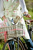 Young woman in floral apron on retro bicycle with various rose-patterned fabrics in front basket