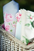 Various rose-patterned fabrics in wicker basket