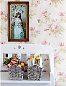 Framed photograph above baskets of garden roses on white wooden bench against rose-patterned wallpaper