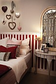 Scatter cushions on bed against half-height, red and white striped wood panelling in bedroom