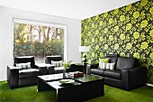 Dark leather sofa set against green retro wallpaper combined with green velour carpet; large picture window showing view of garden