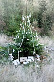 Christmas tree decorated with baubles, garlands and wrapped presents in woodland clearing