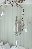 Glass and white china animal figurines hanging from branch as Advent decoration