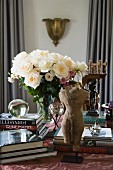 Miniature stone torso sculpture and books stacked around vase of white roses on table