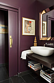 Modern washstand with white basin on wooden counter in purple-painted bathroom with open sliding door