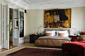 Grand bedroom with open double doors and double bed against wall below modern artwork