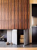 Fitted cupboards with grey doors and doors veneered in African wood next to open-plan kitchen