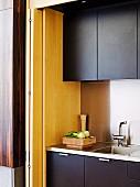 Detail of modern kitchen with dark cupboard doors next to folding door