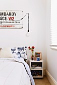 Bedroom with street sign on wall and retro bedside cabinet