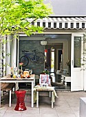 Set table in courtyard with view into open-plan living area with bicycle hanging on wall
