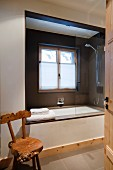 View through open door of rustic wooden chair and modern bathtub integrated into window niche
