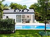 Large swimming pool in extensive garden; white summer house with open terrace doors in background