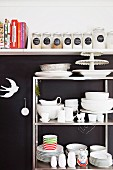Metal shelves of white crockery against black wall below white, wall-mounted kitchen shelf of cookery books and storage jars
