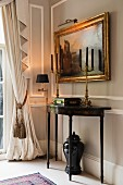 Bronze candelabras on 18th century console table and antique painting on stone grey wall; draped curtain with pelmet