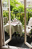 Afternoon tea on small steel balcony with climber-covered balustrade; view through open lattice window