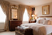 Antique chests of drawers, draped curtains and elegant trunk at foot of double bed in traditional bedroom