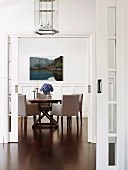 View into elegant, high-ceilinged dining room with wooden table and upholstered chairs; landscape photograph on white wall