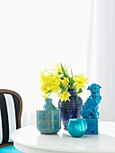 Bouquet of daffodils in blue ceramic vase on white table