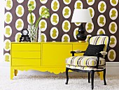 Flower arrangement and table lamp on yellow sideboard against wallpaper with brown and yellow pattern and behind comfortable upholstered armchair