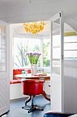 Einblick in helles Zimmer mit orangem Drehsessel im Retrostil vor rundem Holztisch