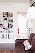 White built-in shelf with square compartments; in front of it a plush, brown sofa
