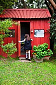 Red garden shed with a corrugated iron roof
