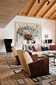 Sessel mit Holz Armlehnen und Sofa auf Teppich mit geometrischem Retromuster im Wohnzimmer mit rustikal modernem Flair