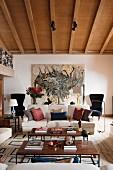 Couchtische im 60er Jahre Stil und Sofa mit verschiedenen Kissen im Wohnzimmer mit Holzbalkendecke