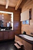 Chalet bathroom - wood-clad bathtub with steps opposite washstand with base cabinets and illuminated mirror