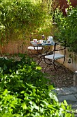 Secluded seating area in Mediterranean garden with wrought iron chairs and table set for two for afternoon coffee