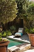 Sonnenliege auf hölzernem Pooldeck zwischen mediterranen Pflanzen