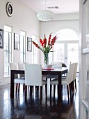 Red gladioli on large dining table and chairs with leather upholstery in classic black and white dining room